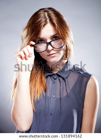 Strict serious young woman holding large nerd glasses - stock photo