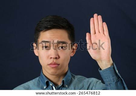 Strict young Asian man giving the stop sign and looking at camera - stock photo