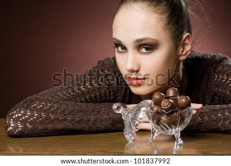 Striking beautiful brunette girl with tasty chocolate. - stock photo