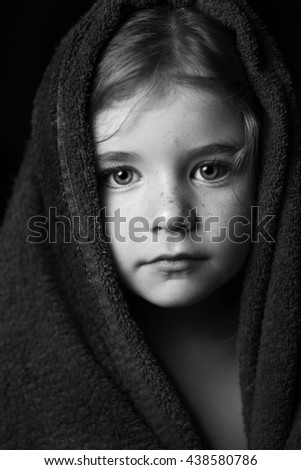 Striking black and white portrait of young girl wrapped in a bath towel.