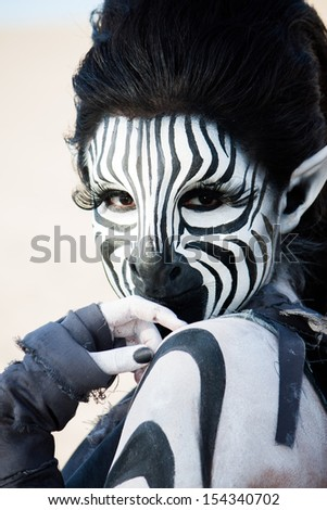 striking black and white zebra woman looks demurely over her shoulder.  Fabulous special fx make up by Rayce Bird - stock photo