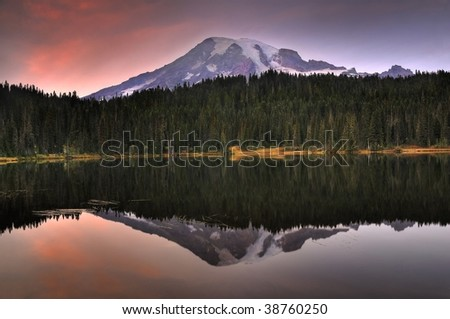 Striking image of Mount Rainier perfectly reflected across the reflection lakes at dusk - stock photo