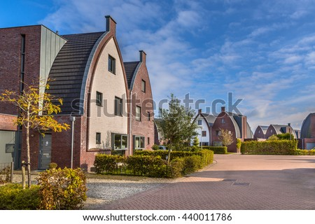 Striking modern suburban family houses in a child-friendly  neighborhood with trees and playground - stock photo