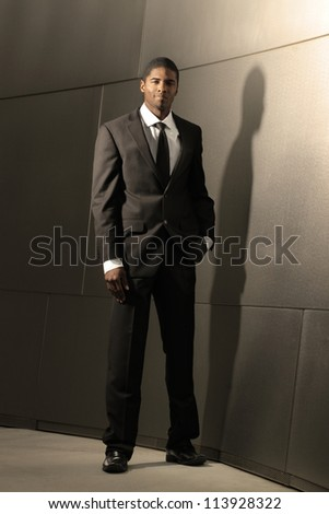 Striking portrait of a young good looking successful businessman in suit leaning against modern shiny building - stock photo
