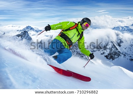 Striking shot of a colorful clothed freerider skiing the snow wave.
