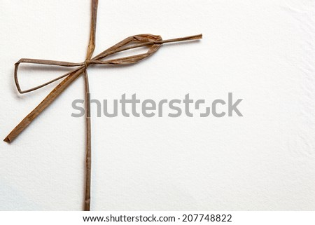 String bow on textured white paper. - stock photo