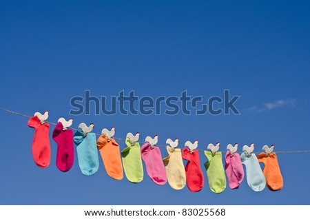 String of colorful socks against sunny blue sky in the garden - stock photo