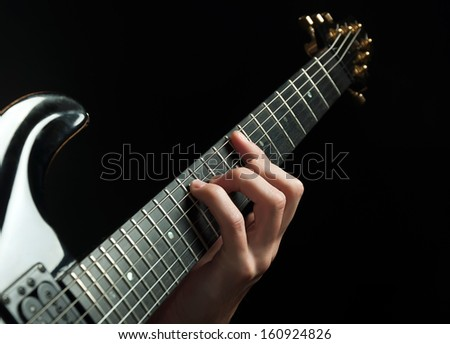 strings and guitarist hand playing guitar over black - shallow DOF with focus on hand - stock photo