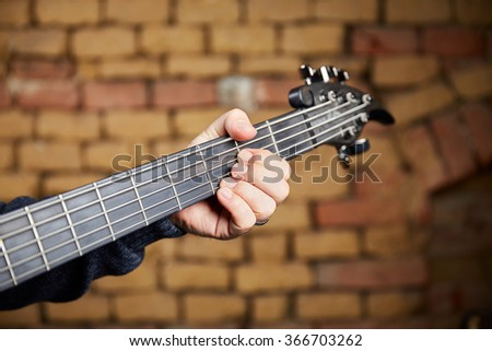 Strings and the head of a bass guitar with the fingers of the musician forming a riff. - stock photo