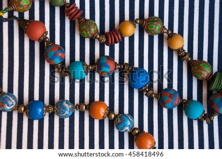 Strings of indian beads. Background with jewelry. Bohemian necklaces on striped fabric.Handmade jewelry of polymer clay. - stock photo