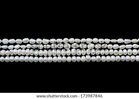 Strings of white pearl isolated over black - stock photo