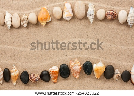 Stripe of sea shells and stones lying on the sand, with space for text - stock photo