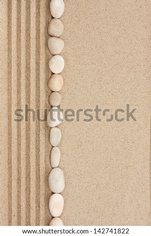 Stripe of white stones lying on the sand with space for text - stock photo