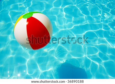 striped ball in the pool sunny day and waves - stock photo