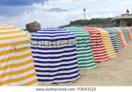 Striped beach tents on sand, facing the ocean, Biarritz - stock photo
