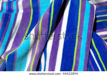 striped beach towel useful as a background texture - stock photo