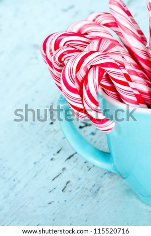 Striped Christmas candy canes in a light blue / turquoise cup with shabby chic wooden background - stock photo