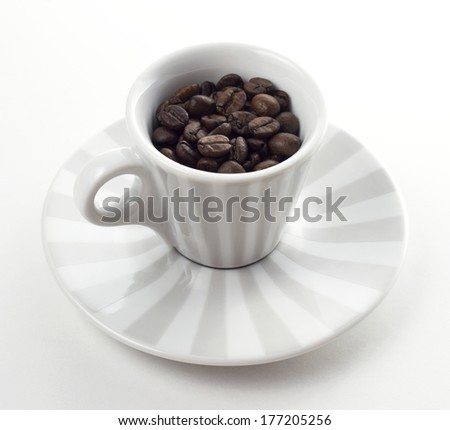 striped cup and plate with roasted coffee beans - stock photo