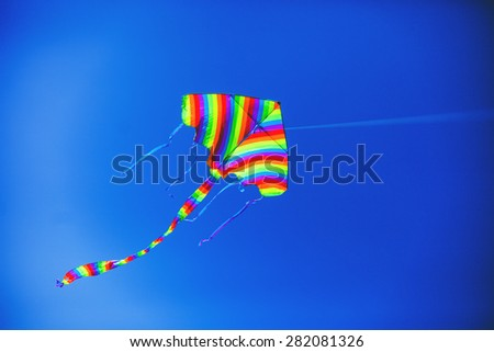 Striped kite flying against the blue sky on a sunny day - stock photo