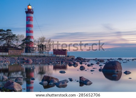 Striped lighthouse at night time with rocks in still water on foreground