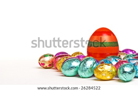 Striped orange easter egg surrounded by foil wrapped eggs.