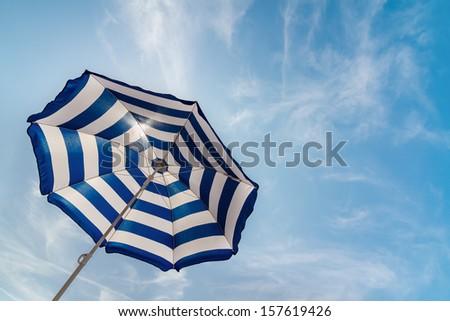 Striped sun umbrella under brightly shining sun - stock photo
