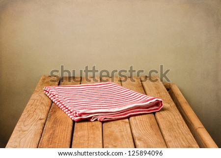 Striped tablecloth on wooden deck table over grunge background - stock photo