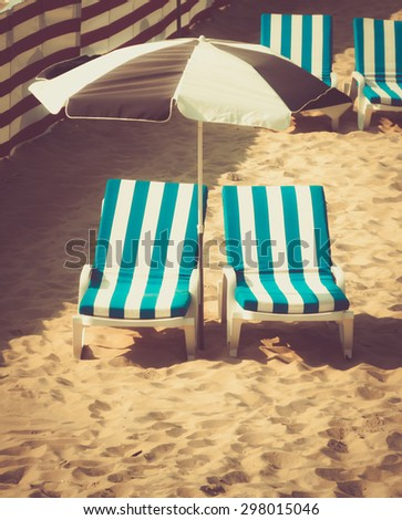 Striped turquoise chairs with umbrella on beach in sunlight, retro toned - stock photo