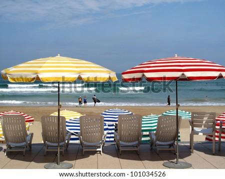 Striped umbrellas on the  beach, facing the ocean, Biarritz, France. - stock photo