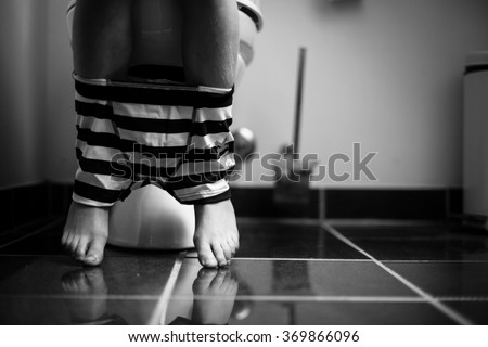 Striped Underwear Around the Legs of a Young Boy Using a Toilet at Home in Monochrome Color. - stock photo