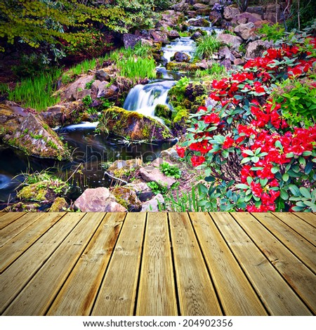 Striped wooden plank terrace with the view to Red Rhododendron flowers and a cascade - stock photo