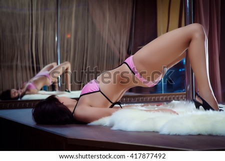 Stripper. Sexy girl dancing striptease. Model of the pylon. Sexy girl in the mirror with a pylon. Erotic dance. Massage parlor. Escort. - stock photo
