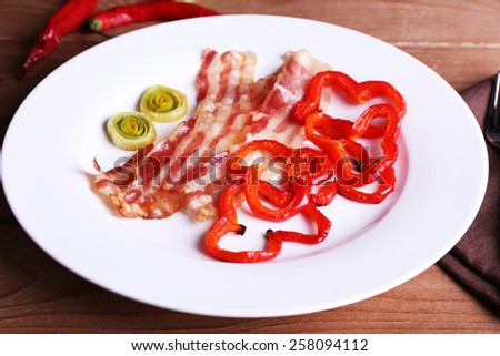 Strips of bacon with sliced shallot and pepper in plate on wooden table background