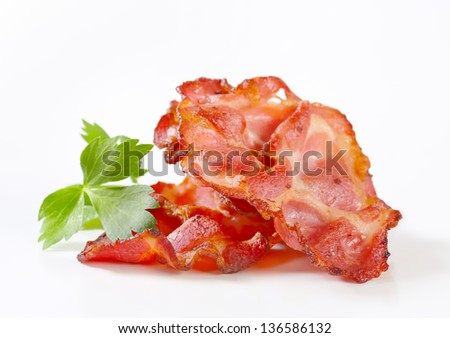 Strips of crispy fried bacon isolated on white - stock photo