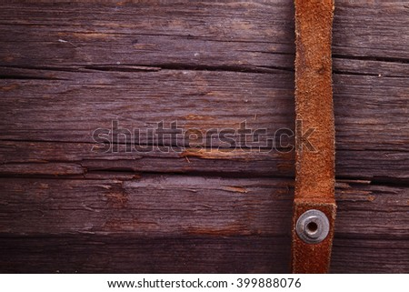 Strips of leather on a wooden plank. The distinctive cowboy detail - stock photo