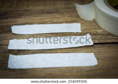 Strips of masking tape on wood. - stock photo