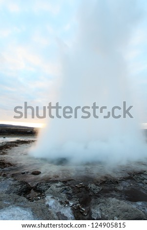 Strokkur Geyser in Iceland erupting at sunset in winter