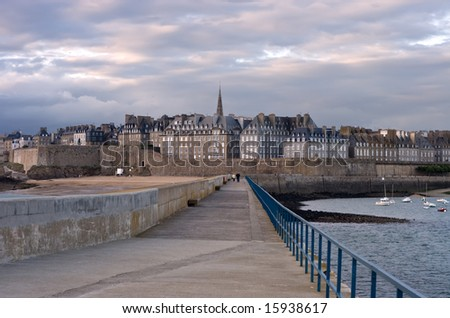 Strolling the pier in Saint Malo in late afternoon with the walled city directly in front view, France - stock photo