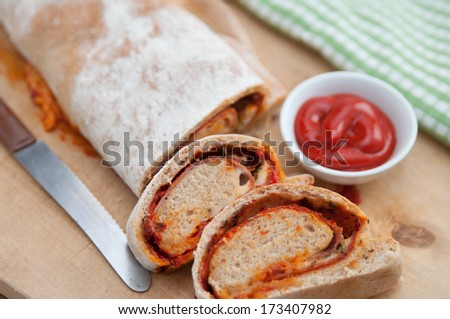 Stromboli - italian sandwich filled with ham and cheese  - stock photo