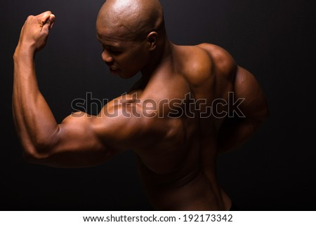strong african american bodybuilder posing on black background - stock photo