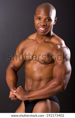 strong african american man flexing muscle over black background - stock photo