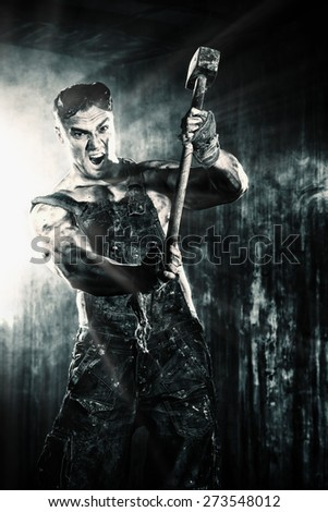Strong aggressive coal miner with a hammer over dark grunge background. Mining industry. Art concept. Toned photo, old style. - stock photo