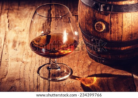 Strong alcohol on a wooden table and barrel - stock photo