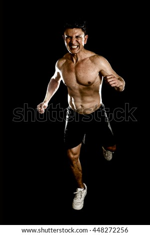 strong and fit man with ripped body muscles running determined and hard doing sprint workout with naked torso isolated on black background in sport condition and training concept - stock photo