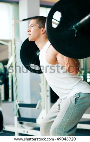 Strong and handsome man lifting weights - a barbell - in a gym - stock photo