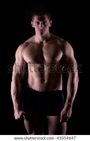 strong and harebrained athlete on dark background - stock photo