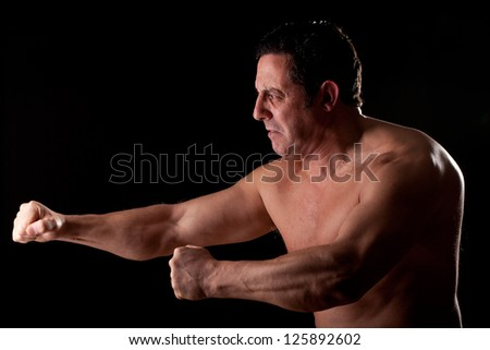 strong and harebrained strong man on dark background - stock photo
