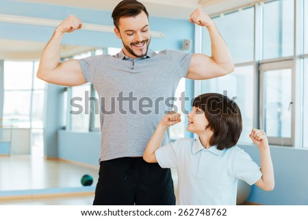 Strong and healthy. Happy father and son showing their biceps and smiling while both standing in health club