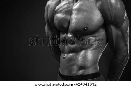Strong and muscular body of man shaded over black background. - stock photo