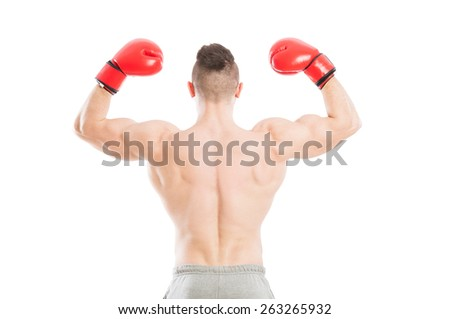 Strong and muscular boxer from behind flexing his arms and wearing red boxing gloves - stock photo